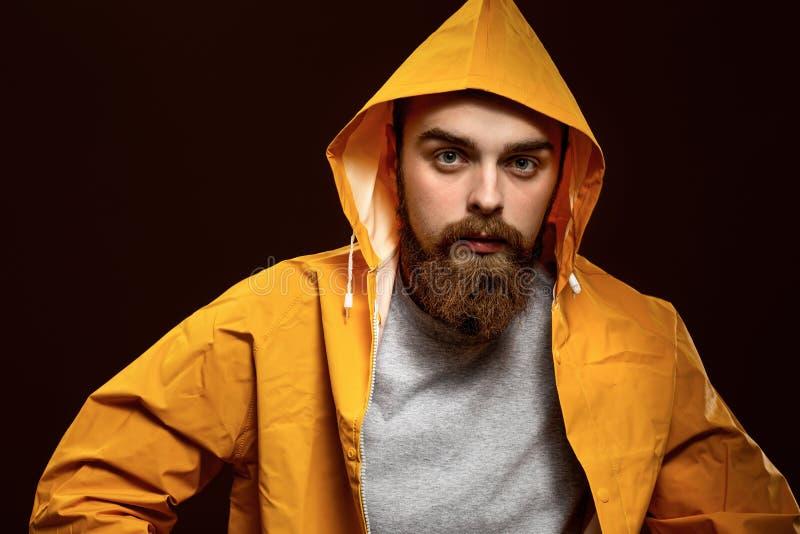 Elegancki miedzianowłosy facet z brodą ubierającymi w wąsy i szarej koszulce żółtej kurtce z kapiszonem i pozuje na a zdjęcie royalty free
