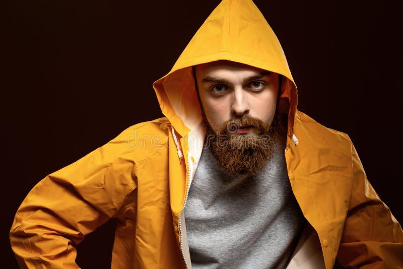 Elegancki miedzianowłosy facet z brodą ubierającymi w wąsy i szarej koszulce żółtej kurtce z kapiszonem i pozuje na a zdjęcia royalty free