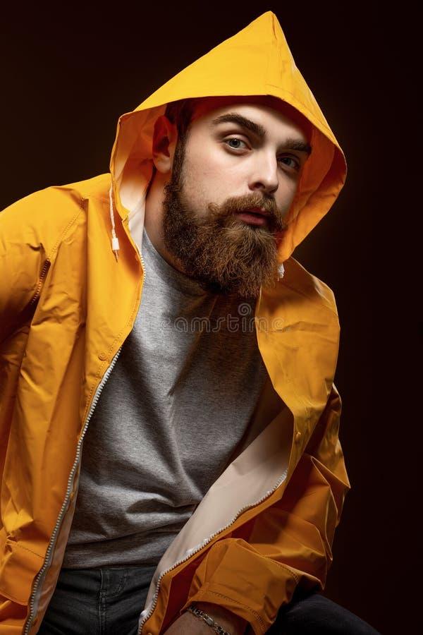Elegancki miedzianowłosy facet z brodą ubierającymi w wąsy i szarej koszulce żółtej kurtce z kapiszonem i pozuje na a obraz royalty free