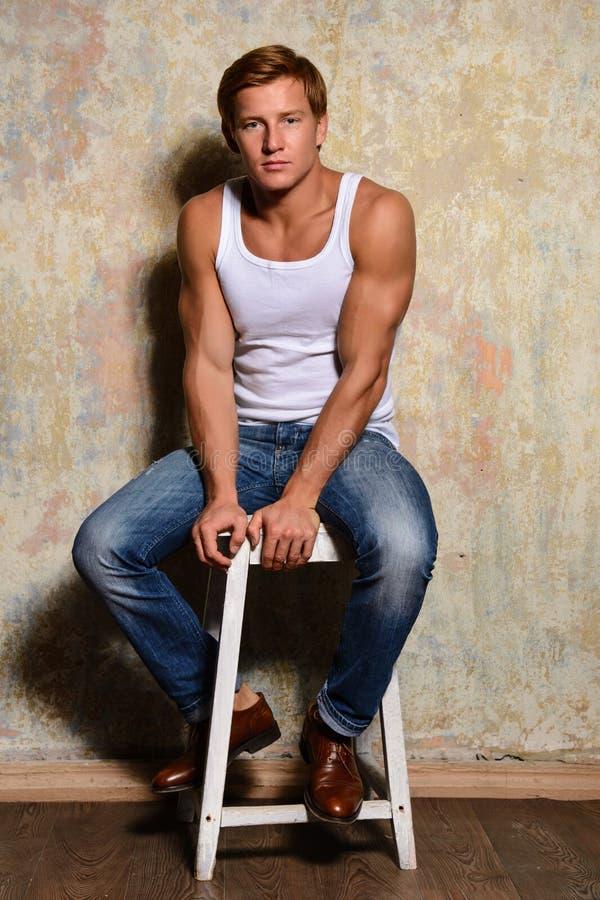 Elegancki moda mężczyzna modela obsiadanie na krześle fotografia royalty free