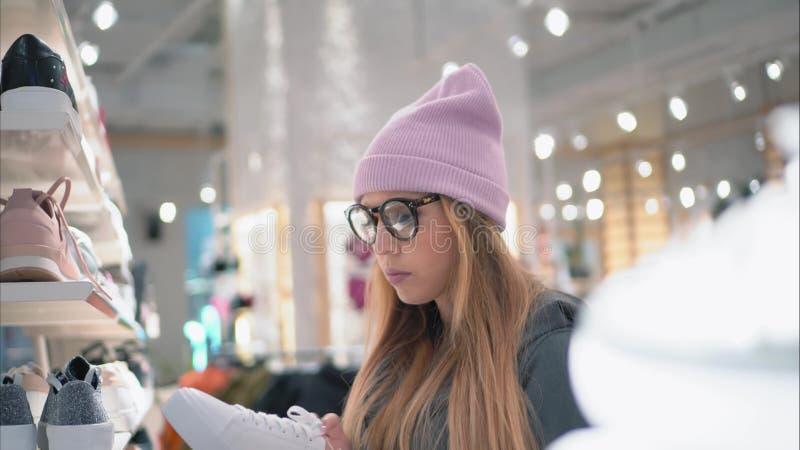 Elegancki modniś dziewczyny komes obuwianego sklepu stojak i wybiera nowych sneakers fotografia stock