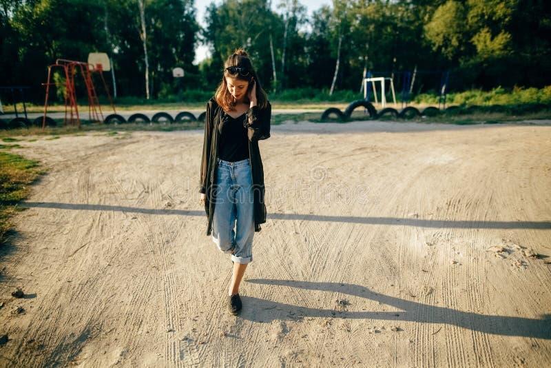 Elegancki modniś dziewczyny odprowadzenie w pogodnej ulicie, atmosferyczny moment Modna chłodno kobieta z czarnymi okularami prze obraz stock