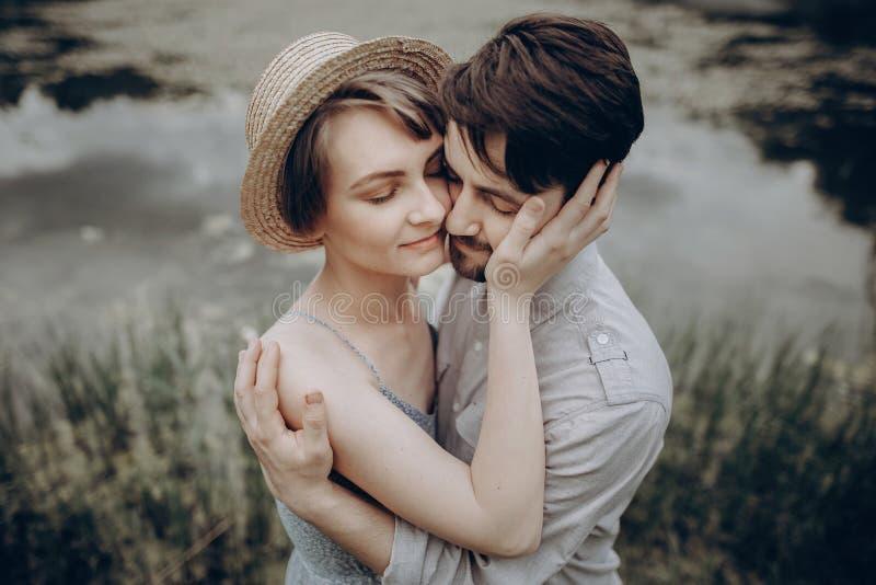 Elegancki modniś pary przytulenie przy jeziorem mężczyzna i kobieta w nowożytnym obraz royalty free