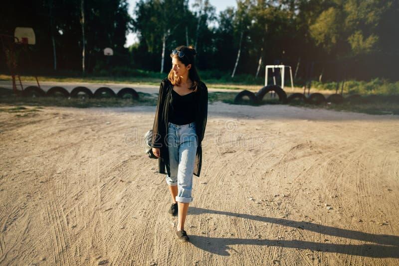 Elegancki modni? dziewczyny odprowadzenie w pogodnej ulicie, atmosferyczny moment Modna ch?odno kobieta z czarnymi okularami prze obraz stock