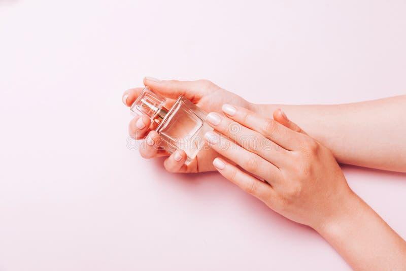Elegancki modny ?e?ski manicure Kobiet ręki trzyma pachnidło butelkę na różowym tle Odg?rny widok, mieszkanie nieatutowy obraz stock