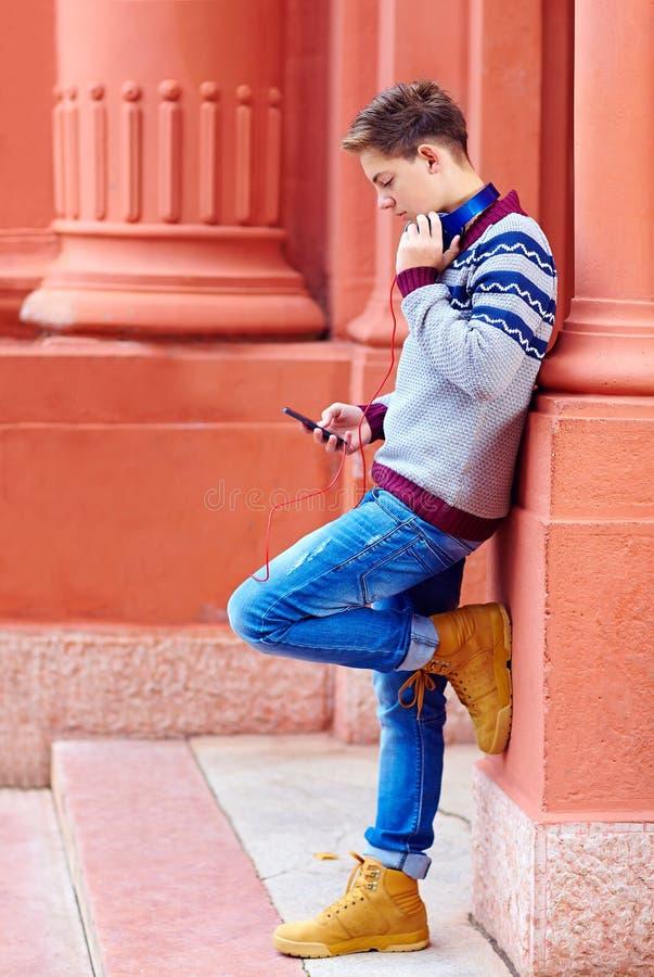Elegancki nastoletni chłopak słucha muzyka na mądrze telefonie obraz royalty free