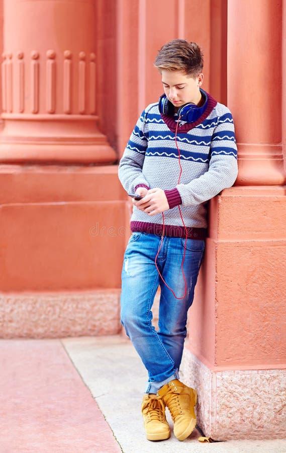 Elegancki nastoletni chłopak słucha muzyka na mądrze telefonie fotografia royalty free