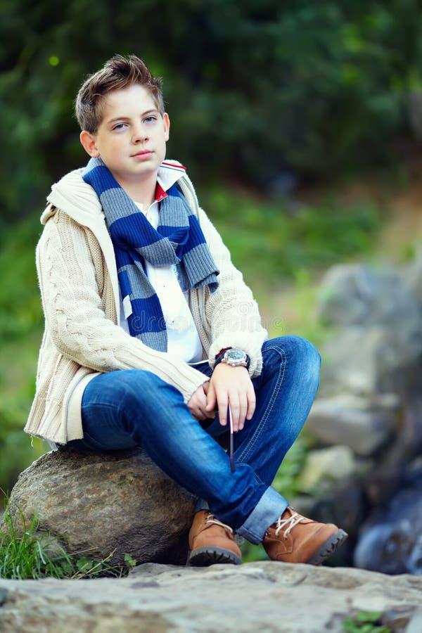 Elegancki nastoletni chłopak siedzi na skale elegancki, natura zdjęcie royalty free