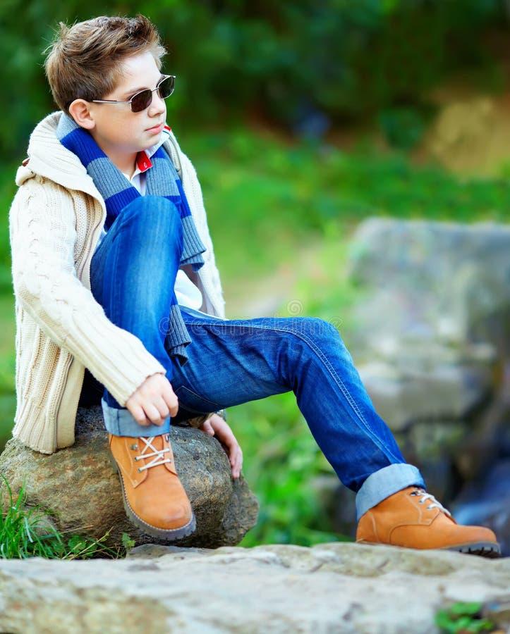 Elegancki nastoletniego chłopaka obsiadanie na skale outdoors zdjęcia stock
