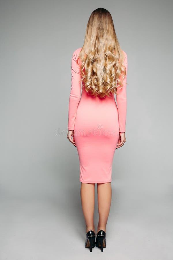 Elegancki oszałamiająco model w przypadkowej przytulenie menchii sukni i piętach obrazy royalty free