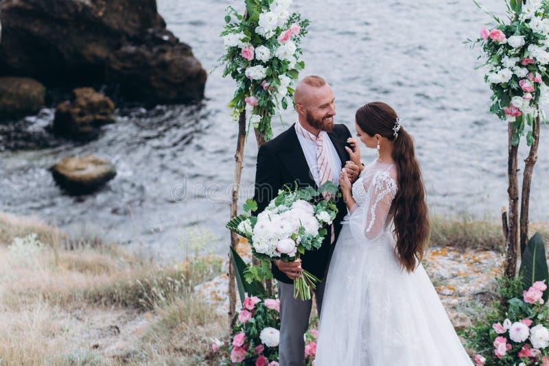 Elegancki państwo młodzi przysięga hołdownictwo na plaży pod łukiem dekorującym z świeżymi kwiatami obraz stock