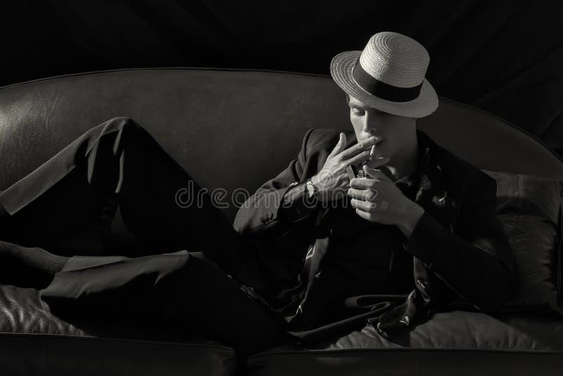 Elegancki palacz Modny młody człowiek Zaświeca papieros fotografia royalty free