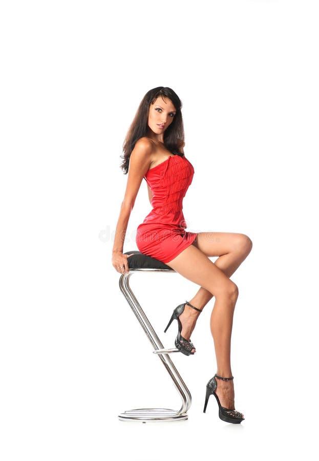Elegancki piękny kobiety obsiadanie na współczesnej metal prętowej stolec, odizolowywającej na bielu obraz stock