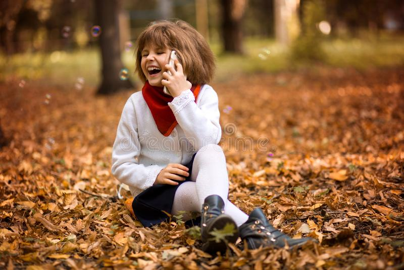 Elegancki piękny małej dziewczynki mienia telefon komórkowy i uradowanie opowiadamy obraz stock