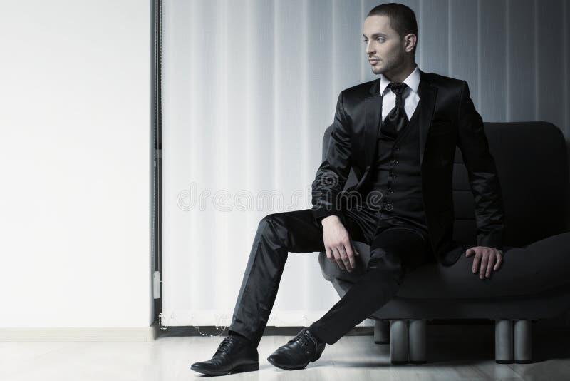 Elegancki potomstwo mody mężczyzna w smokingu na kanapie, fotografia royalty free