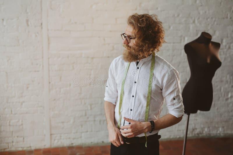 Elegancki projektant w pracowniany patrzeć daleko od obrazy stock