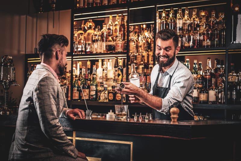 Elegancki przygotowywający mężczyzna pije alkohol przy barem zdjęcia stock