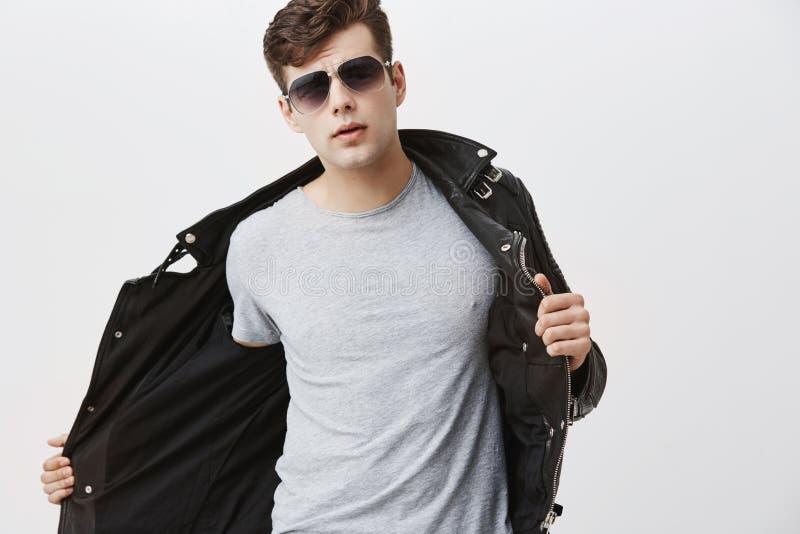 Elegancki przystojny atrakcyjny Europejski młody człowiek z modnym ostrzyżeniem ubierał w modnej czarnej skórzanej kurtce, jest u obrazy royalty free