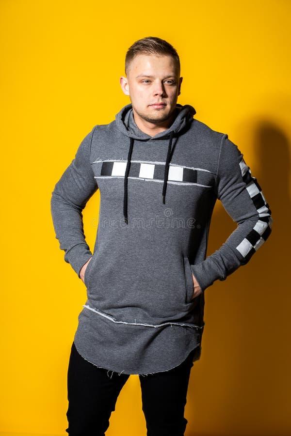Elegancki przystojny młody człowiek z ostrzyżeniem w moda puloweru pozach fotografia royalty free
