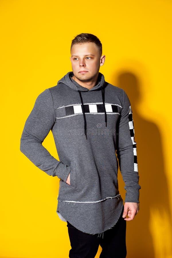 Elegancki przystojny młody człowiek z ostrzyżeniem w moda puloweru pozach zdjęcia stock