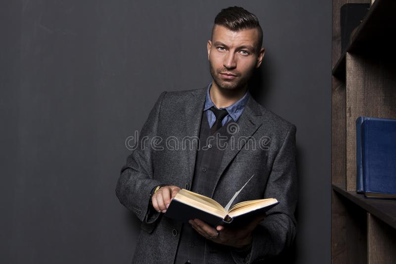 Elegancki przystojny elegancki mężczyzna w garniturze z książką zdjęcia royalty free
