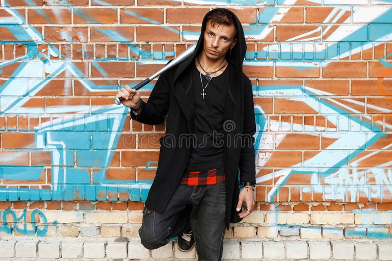 Elegancki przystojny mężczyzna z nietoperzem pozuje blisko ściana z cegieł z zdjęcia royalty free