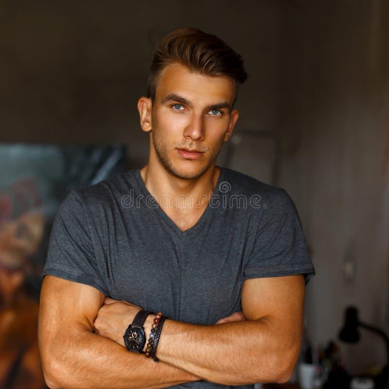 Elegancki przystojny młody człowiek z ostrzyżeniem w szarej koszulce zdjęcia royalty free