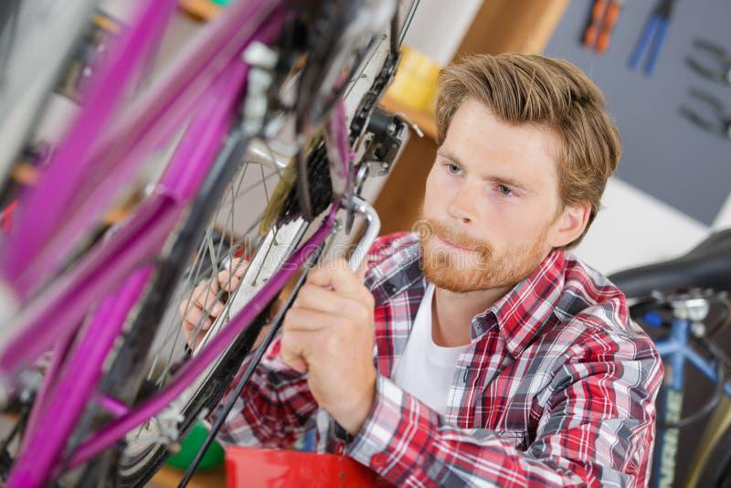 Elegancki rowerowy mechanik robi fachowej pracie w warsztacie zdjęcia royalty free