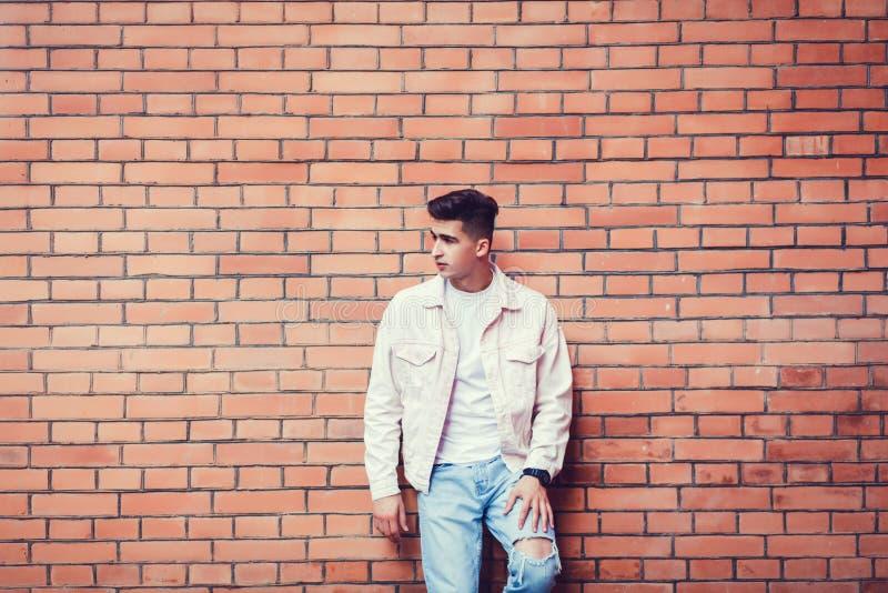 Elegancki seksowny mężczyzna pozuje blisko cegły zdjęcie royalty free