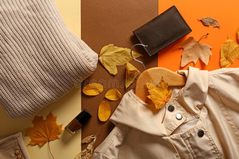Elegancki strój z gwoździa połyskiem i jesień liśćmi na koloru tle, odgórny widok obrazy stock