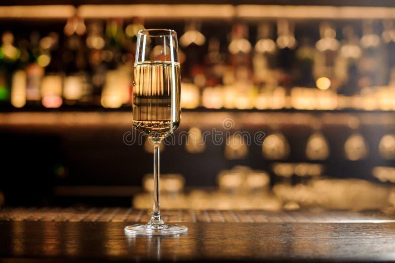 Elegancki szampański szkło z iskrzastym winem na prętowym kontuarze zdjęcia stock