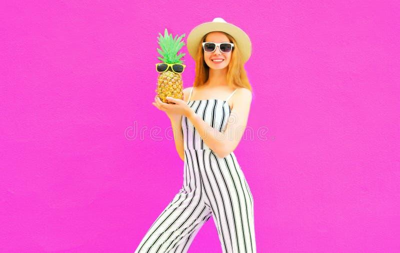 Elegancki szczęśliwy uśmiechnięty kobiety mienia ananas jest ubranym pasiastego kombinezon, lata round słomiany kapelusz na kolor obrazy royalty free