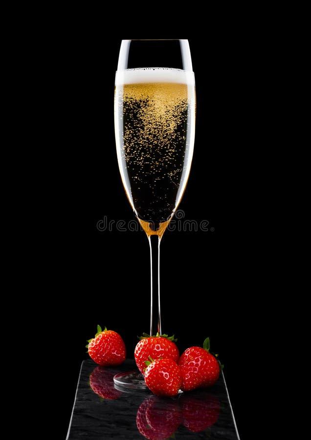 Elegancki szkło żółty szampan z świeżymi stawberries na czerń marmuru desce na czarnym tle zdjęcia royalty free