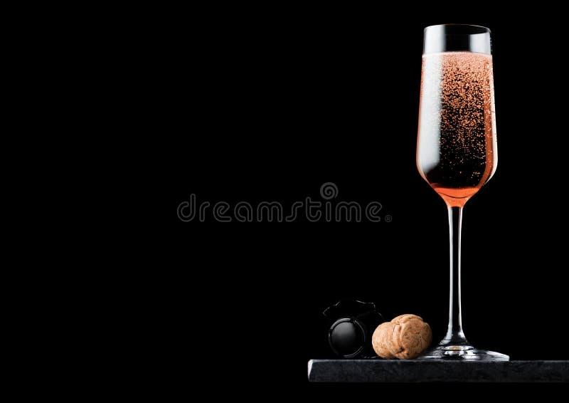 Elegancki szkło menchii róży szampan z korka i drutu klatką na czerń marmurze wsiada na czarnym tle Przestrzeń dla teksta fotografia royalty free