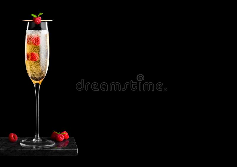 Elegancki szkło żółty szampan z, świeże jagody z nowym liściem na kiju na czerni i wykładamy marmurem bo fotografia stock