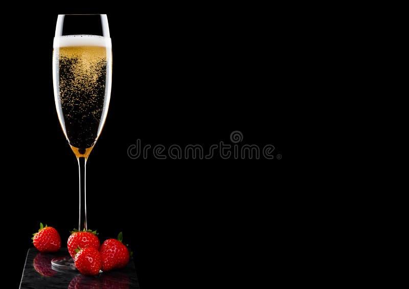 Elegancki szkło żółty szampan z świeżymi stawberries na czerń marmuru desce na czarnym tle Przestrzeń dla teksta obraz royalty free