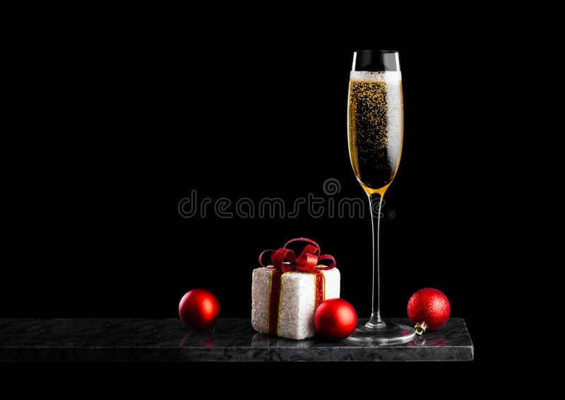 Elegancki szkło żółty szampan z bąblami z boże narodzenie nowego roku prezenta zabawkami na marmur desce na czarnej tło przestrze zdjęcie stock