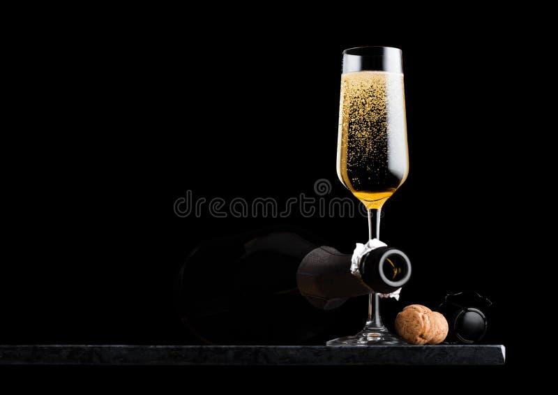 Elegancki szkło żółty szampan z klatką, butelka na czerń marmurze i wsiadamy na czarnym tle Przestrzeń dla teksta obraz stock