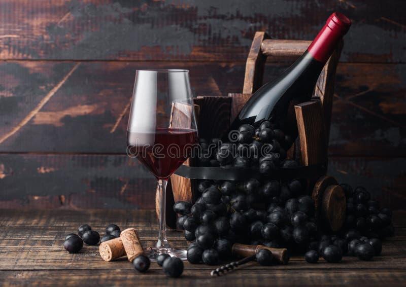 Elegancki szkło czerwone wino z ciemnymi winogronami i butelką wino wśrodku rocznik drewnianej baryłki na ciemnym drewnianym tle  zdjęcia stock
