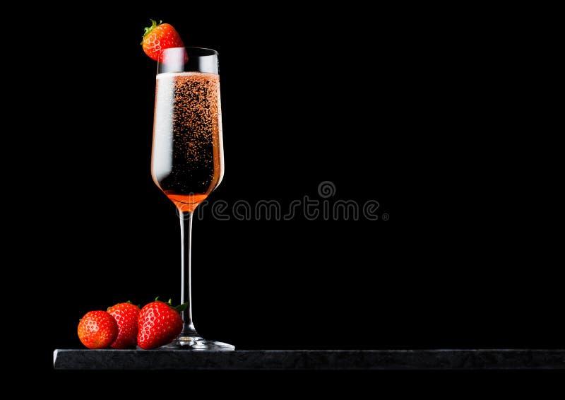 Elegancki szkło menchii róży szampan z truskawką na odgórnych i świeżych jagodach na czerń marmuru desce na czarnym tle Przestrze zdjęcia stock
