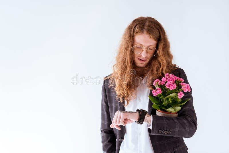 elegancki tatuujący biznesmen z kędzierzawego włosy mieniem puszkował kwiaty i sprawdzać czas obraz royalty free