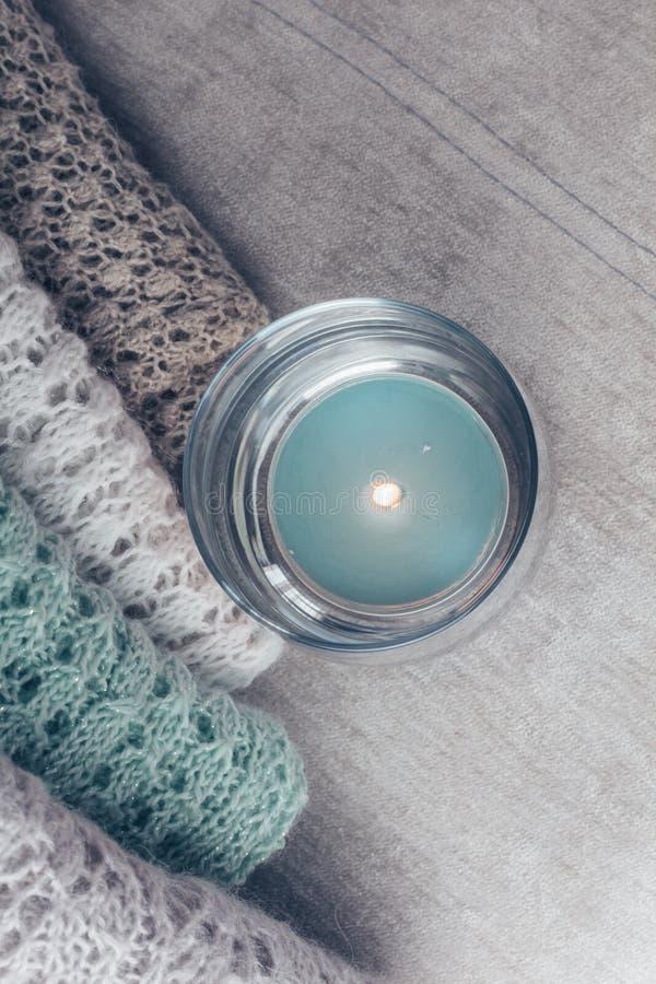 Elegancki trykotowy pastel barwił pulowery wypiętrzających na velvety tkaninie wzdłuż zaświecającej świeczki Odgórny widok, kopii zdjęcie royalty free
