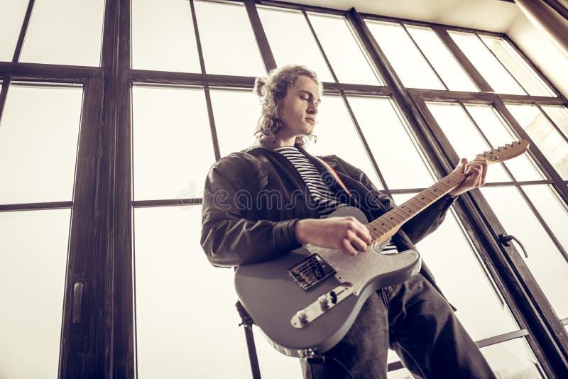Elegancki utalentowany muzyk cieszy się bawić się hard rock muzykę zdjęcia royalty free
