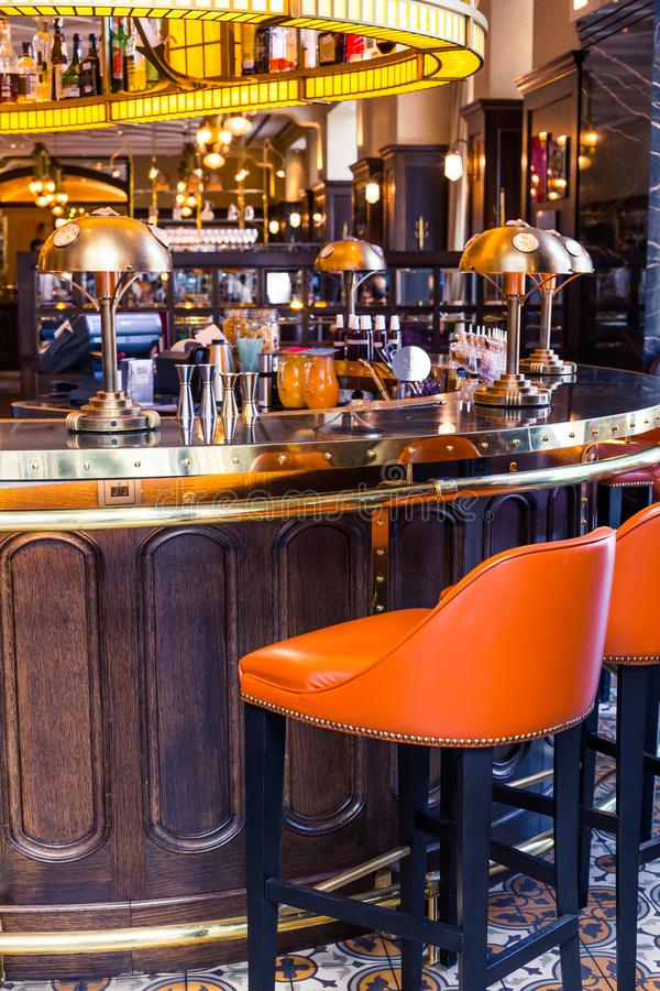 Elegancki wnętrze bar w rocznika stylu, Pomarańczowi krzesła, szkła, lampy i projektant dekoracje, fotografia stock
