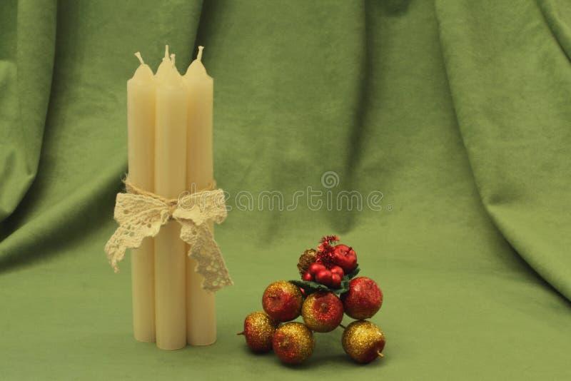 Eleganckie świeczki wiązali z koronkowym faborkiem i jaskrawym dekoracyjnym bukietem jabłka na zielonym tle boże narodzenie izola fotografia stock