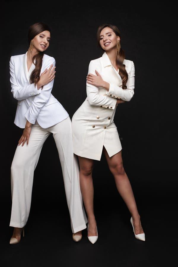 Eleganckie kobiety w białym mądrze kostiumu i smokingowym pozować zdjęcie royalty free