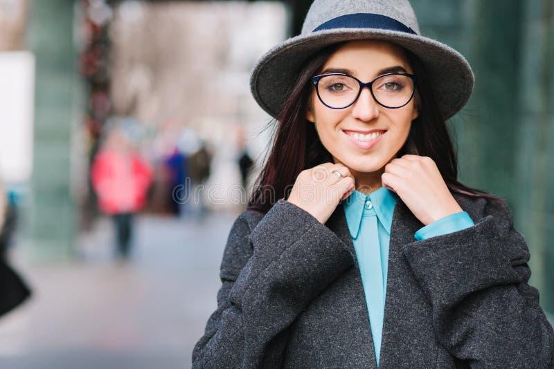 Eleganckiego miasto portreta młoda ładna kobieta w popielatym kapeluszu, czarni szkła chodzi na ulicie w centre Luksusowy żakiet fotografia stock