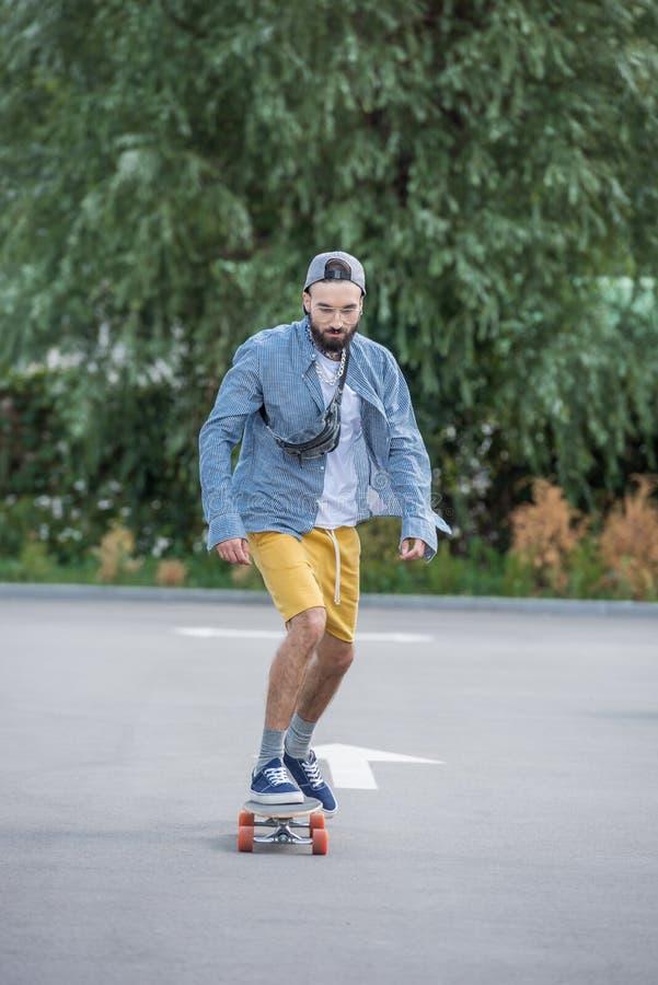 Eleganckiego modnisia mężczyzna jeździecki longboard na ulicie zdjęcie stock