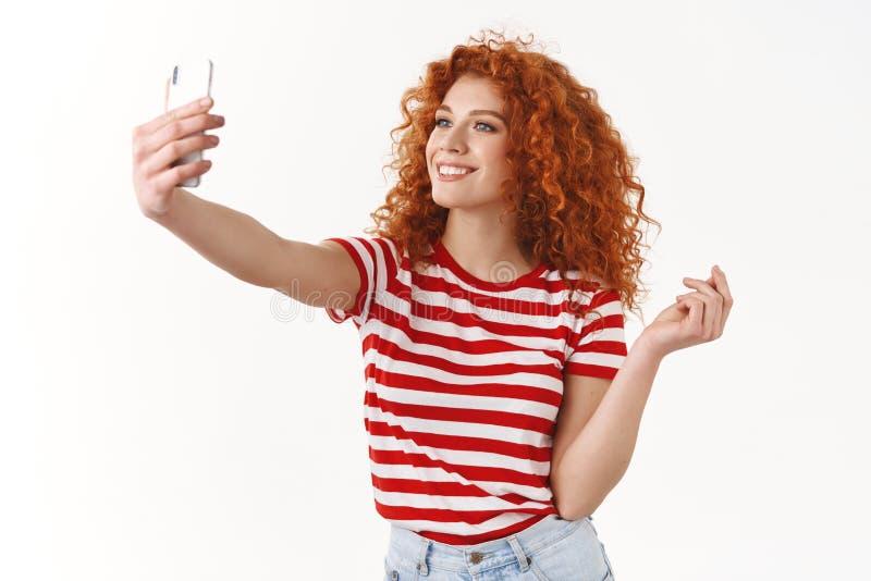 Eleganckiej atrakcyjnej rudzielec z włosami dziewczyny modna strajkowa poza bierze selfie chwyta smartphone pokazuje ogólnospołec zdjęcie stock