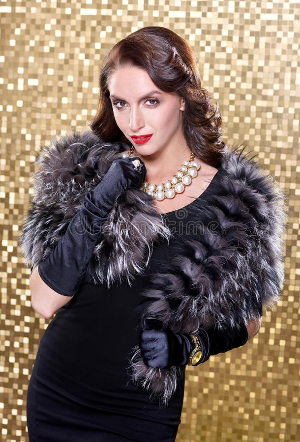 Eleganckiej brunetki retro kobieta jest ubranym srebnego lisa futerko nad złocistym mozaiki tłem Model Patrzeje kamerę zdjęcia royalty free